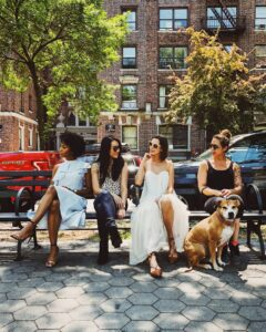 Four women in a bench and a dog.
