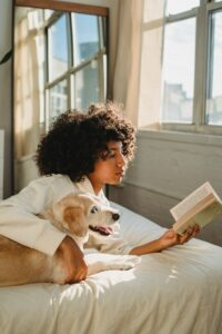 Woman reading with her dog.