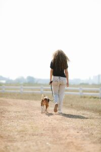 Woman walking her dog by countryside.