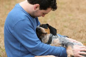 Dog snuggling a man with blue shirt.