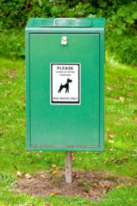Green trash bin for dog waste.