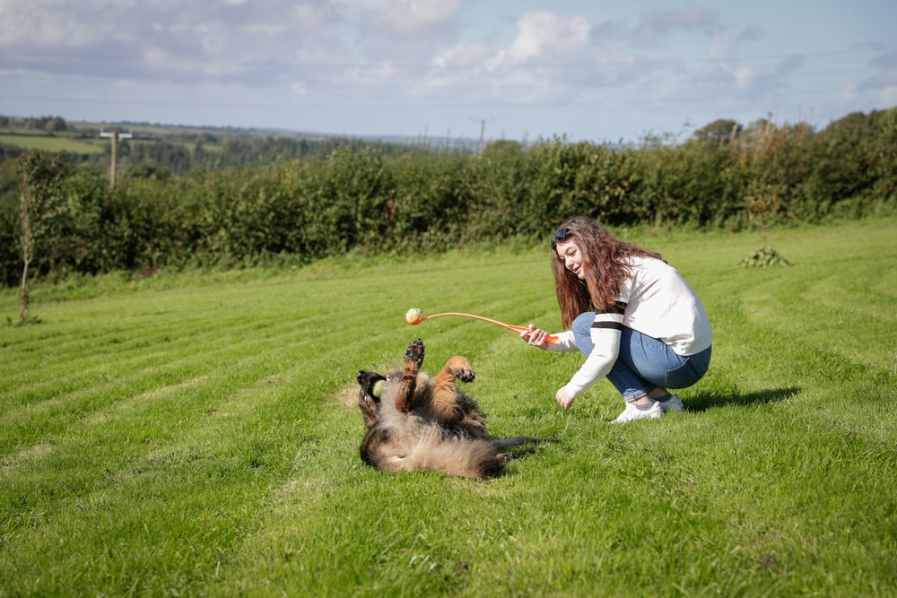 Woman showing how to teach a dog to roll over.